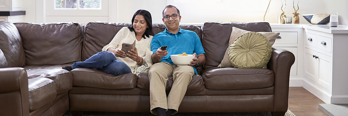 Couple in living room with remote and tablet