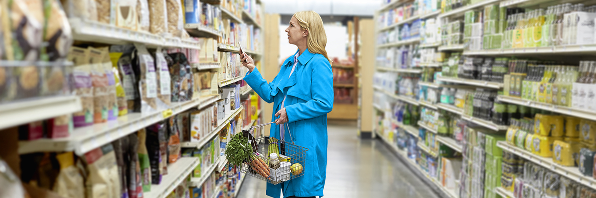 Woman with smartphone in a grocery store